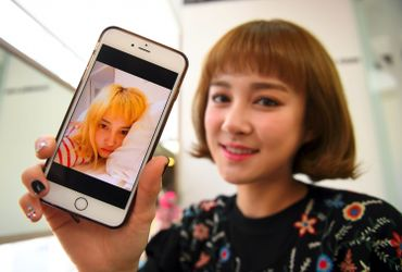 Le 16 mars 2017 à Séoul, Kim Day-Youg (Dain), principale chanteuse de SixBomb, montre une photo d'elle avant les opérations subies pour renforcer sa poitrine et réduire ses pommettes, afin de rendre son visage plus petit.