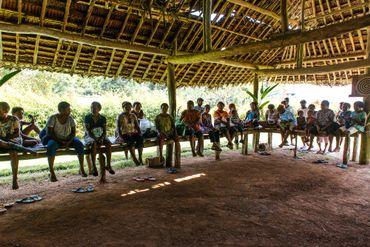Les femmes de la communauté sont réunies sous la grande hutte centrale, elles échangent sur les violences sous le regard de Sophie et des hommes qui participent aux débats.