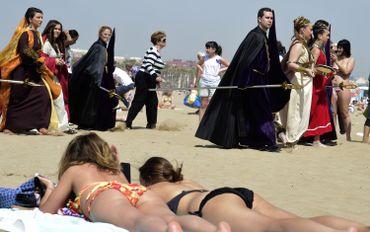 """Procession de la confrérie du """"Christ salvateur"""" à Valence, au milieu des personnes bronzant sur la plage."""