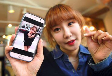 Jung Hye-Yoon (Ga-Bin), membre de SixBomb, montre une photo d'elle avant ses opérations de chirurgie esthétique le 16 mars 2017 à Séoul