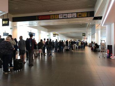 Longue file devant le comptoir Brussels Airlines dans la partie salles d'embarquement de l'aéroport.