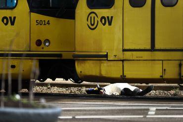 Un corps entièrement recouvert d'un drap blanc se trouve sur les voies du tram, entre deux rames.