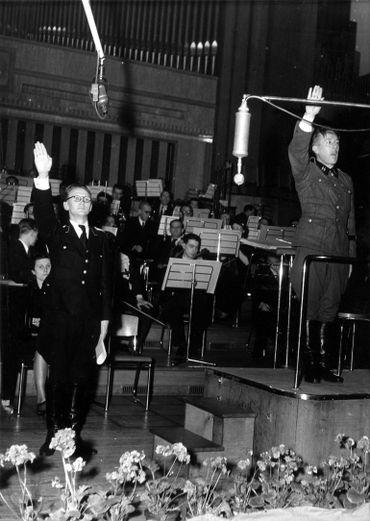 Place Flagey, concert à Radio Bruxelles – Zender Brussel, les radios contrôlées par les Nazis en Belgique pendant la Seconde Guerre mondiale. À droite, le chef de l'orchestre Paul Douliez en uniforme de la Waffen SS