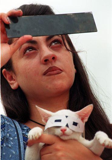 A Islamabad (Pakistan), une jeune femme observe l'éclipse du 11 août 1999, munie de lunettes protectrices. Par humour ou par inquiétude pour la vue du félin, elle a pris soin de protéger les yeux de son chat.