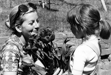 Petite fille offrant des fleurs à sa mère à l'occasion de sa fête, en 1976