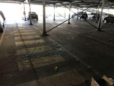 De nombreux bris de verre jonchent le sol du parking