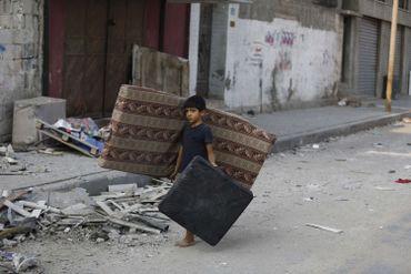 Un garçon palestinien transporte matelas et coussin de la maison démolie de ses parents dans le centre de Gaza city