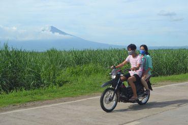 Des motards roulant sur une route avec le volcan Kanlaon en arrière-plan, vu depuis la ville d'Isabela, Negros Occidental, au centre des Philippines, le 24 juin 2020
