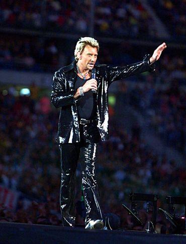 Pour son premier concert au Stade de France, Johnny Hallyday opte pour un costume noir ultra scintillant, visible des 70.000 spectateurs présents. Saint-Denis, septembre 1998