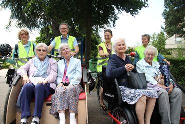 Tim Cooper (en haut à droite sur la photo de gauche) et des seniors à bord de son rickshaw