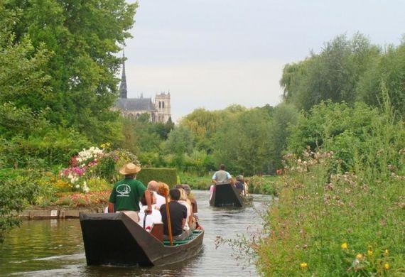 Une promenade en barque au coeur des Hortillonnages d'Amiens, Embarquez votre tribu et laissez-vous guider dans le labyrinthe des jardins flottants à la découverte des traditions maraîchères locales en vraie barque à cornet. Photo : Somme tourisme