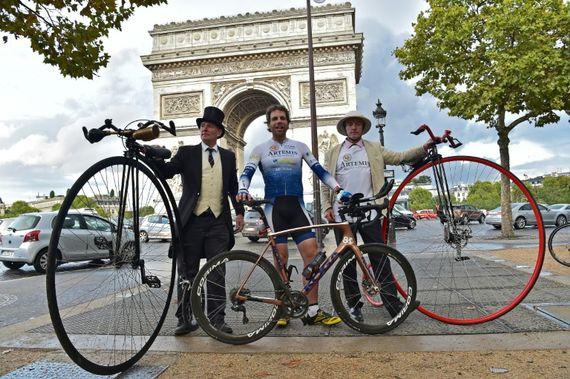 Le cycliste britannique Mark Beaumont (C) pose au côté de deux hommes et leur vélo grand-bi le 18 septembre 2017 à Paris