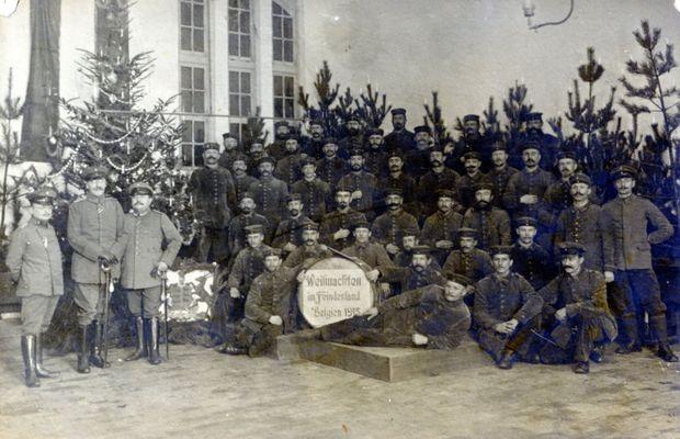 « Noël en pays ennemi : Belgique 1915 ». Une unité allemande est prise en photo en Belgique à la Noël 1915, devant un sapin richement décoré. La mention sur la pancarte rappelle que la fête se fait « en pays ennemi ». La « paix sur terre aux hommes de bonne volonté » devra attendre…  - Collection privée, Nicolas Mignon. ©