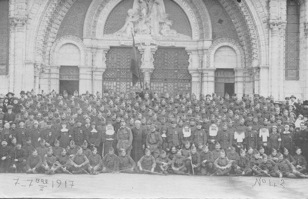 7 septembre 1917. Devant la Basilique Notre-Dame-du-Rosaire de Lourdes, des soldats belges posent pour une photo-souvenir, en compagnie de quelques aumôniers, officiers et religieuses.  - Collection privée, Nicolas Mignon. ©