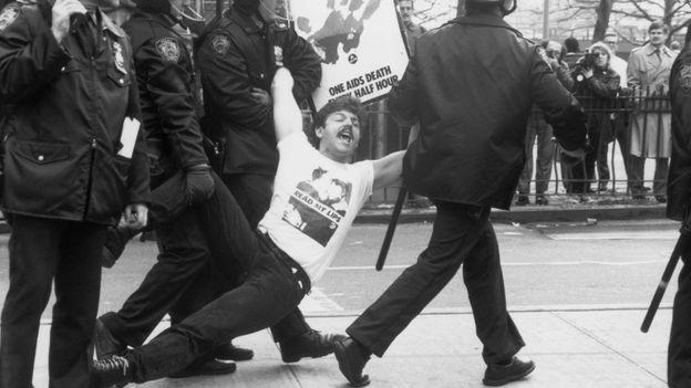 """Des policiers arrêtent et traînent un manifestant lors d'une manifestation ACT UP à New York, en 1989. Il tient une affiche qui dit: """"Le gouvernement a du sang sur ses mains : un mort par sida toutes les demi-heures."""""""