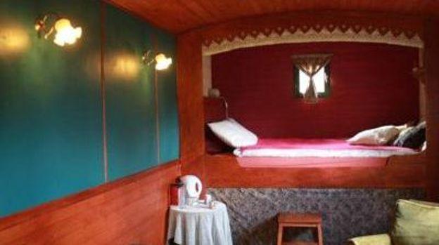 Cette roulotte gitane traditionnelle est installée dans un endroit paisible et verdoyant