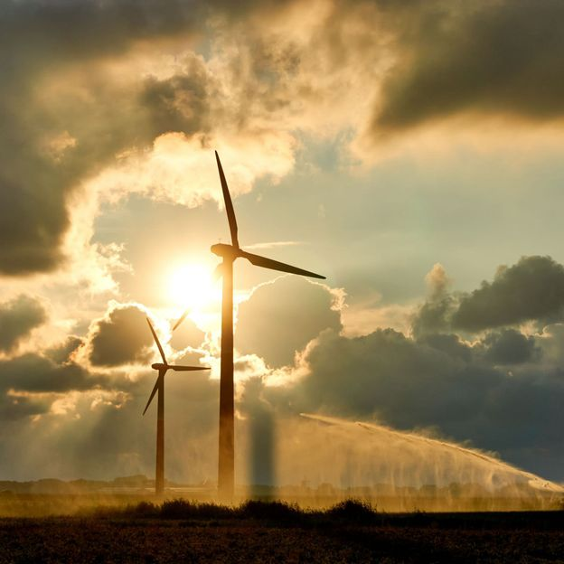 Two wind turbines and irrigating crop water gun or water spray at sunset